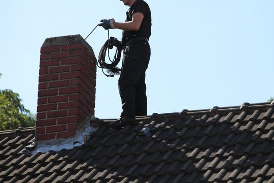 One of our team cleaning a chimney.